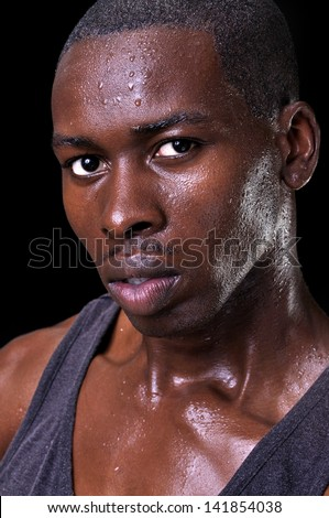 Portrait of attractive young athletic black man with fine facial features on black background - stock photo