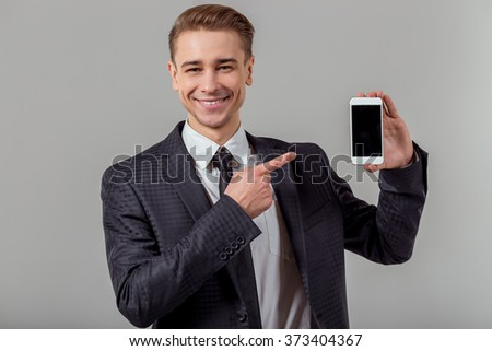 Portrait of attractive young blond businessman in classical suit smiling and pointing on smartphone, standing against gray background