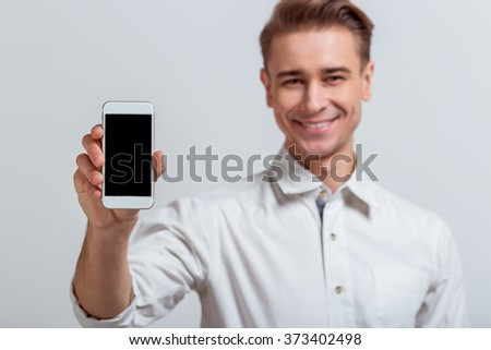 Portrait of attractive young blond businessman in white classical shirt smiling and holding smartphone, standing against gray background - stock photo