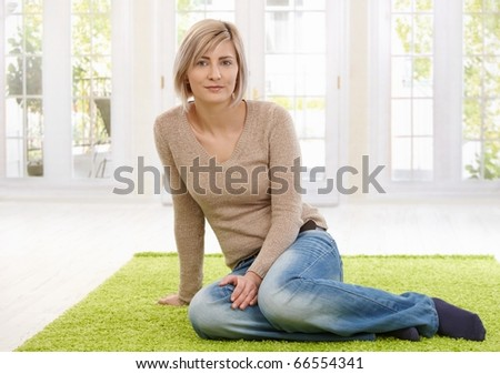 Portrait of attractive young blond woman sitting on floor at home looking at camera, smiling. Copy space for text.? - stock photo