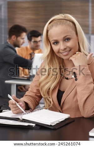 Portrait of attractive young blonde businesswoman sitting at desk, working, smiling, looking at camera. - stock photo