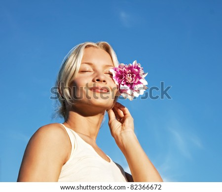 Portrait of attractive young blonde with flower