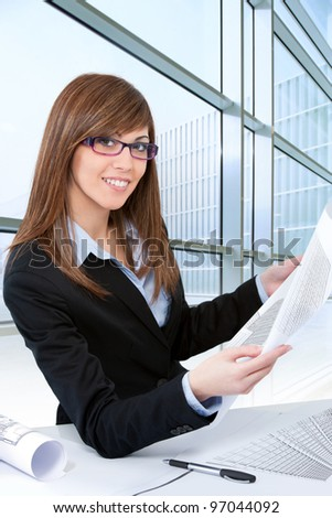 Portrait of Attractive young brunette architect at desk with plans.