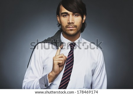 Portrait of attractive young businessman holding his coat over shoulder. Relaxed business executive against grey background. Mixed race male model in formal attire. - stock photo