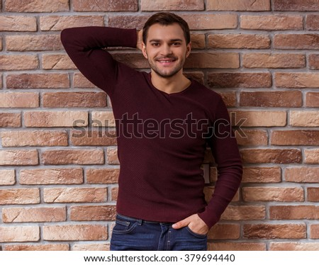 Portrait of attractive young businessman in casual sweater posing, looking in camera and smiling, standing against brick wall - stock photo