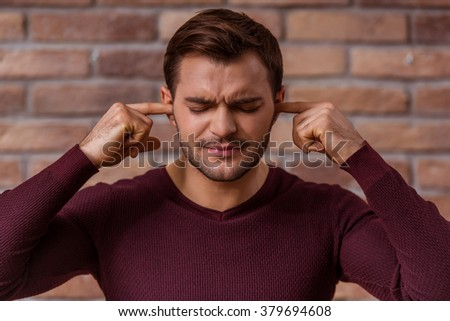Portrait of attractive young businessman in casual sweater showing emotions, covering his ears while standing against brick wall