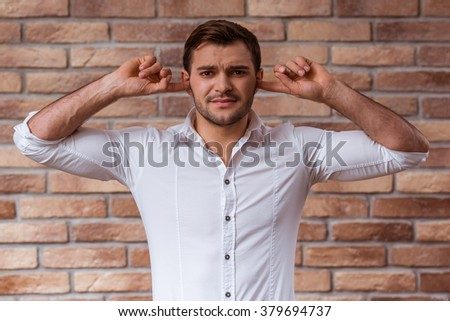 Portrait of attractive young businessman in white shirt showing emotions, covering his ears and looking in camera, standing against brick wall