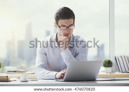 Portrait of attractive young businessman using laptop computer at office desk with coffee cup, paperwork and other items