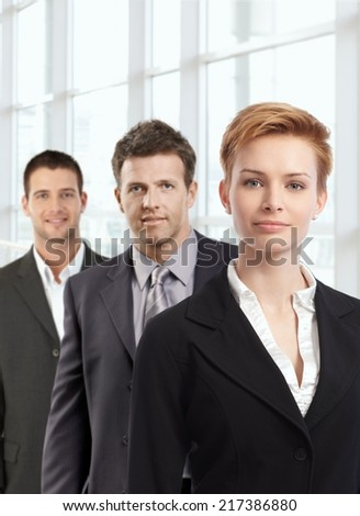 Portrait of attractive young businesswoman and male colleagues at office. - stock photo