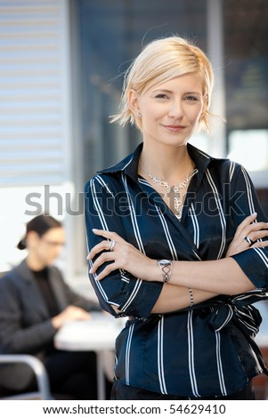 Portrait of attractive young businesswoman standing arms crossed, smiling. - stock photo