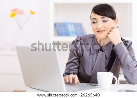 Portrait of attractive young businesswoman thinking over her laptop computer, leaning on her hand. - stock photo