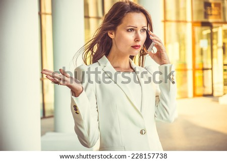 Portrait of attractive young businesswoman with long dark hair and red lips talking on the phone in front of building at sunset. - stock photo