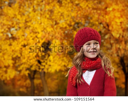 portrait of attractive young caucasian girl in warm colorful clothing  on yellow leaves outdoors smiling looking up