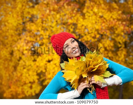 portrait of attractive young caucasian woman in warm colorful clothing  on yellow leaves outdoors smiling looking up