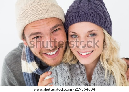 Portrait of attractive young couple in warm clothing over white background - stock photo