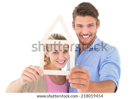 Portrait of attractive young couple looking through house outline over white background - stock photo