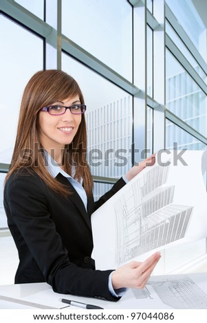 Portrait of Attractive young female architect with plans in office.