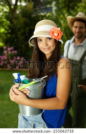 Portrait of attractive young gardening woman holding bucket, smiling happy. - stock photo