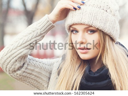 Portrait of attractive young girl in knitted clothes with hand next to her cap. Looking at camera. Outdoors - stock photo