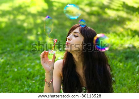 portrait of attractive young girl inflating colorful soap bubbles outdoor