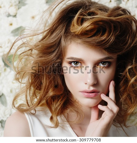 Portrait of attractive young girl on a background of white flowers, the concept of beauty  - stock photo
