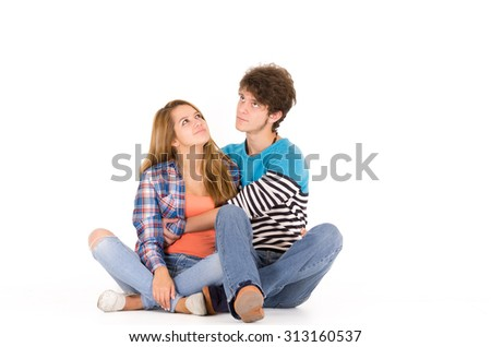 Portrait of attractive young happy couple in love man and woman isolated over white background sitting on floor looking up while dreaming .