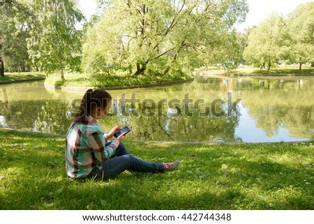 Portrait of attractive young happy girl enjoying her smart phone at the park - stock photo