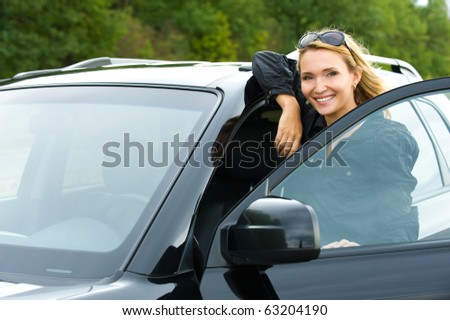 portrait of attractive young happy woman in the new car  - outdoors - stock photo
