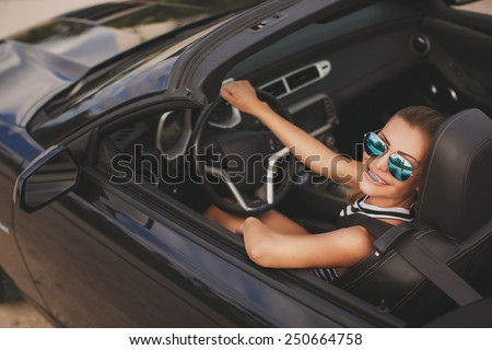 portrait of attractive young happy woman in the new car - outdoors. Portrait of beautiful young woman with makeup in fashion clothes on nature. Beautiful women driving a red car wearing accesoriess - stock photo