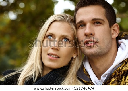 Portrait of attractive young loving couple, looking away. - stock photo