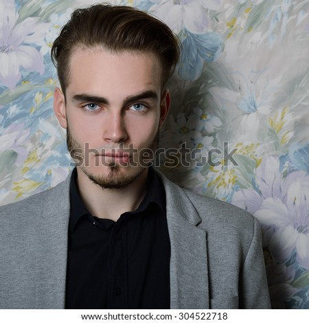 Portrait of attractive young man bites his lip and looking at camera, over floral background. Image toned and noise added. - stock photo