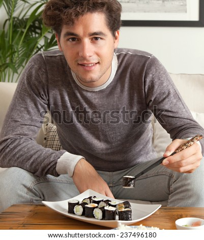 Portrait of attractive young man enjoying eating japanese take away food in living room. Professional man relaxing on home sofa eating exotic food in a stylish home interior. - stock photo