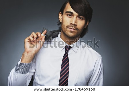 Portrait of attractive young man in formal clothing posing against grey background. Young businessman holding his jacket over his shoulder. Mixed race male model looking at camera. - stock photo