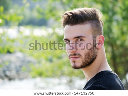 Portrait of attractive young man outdoors, looking in camera - stock photo