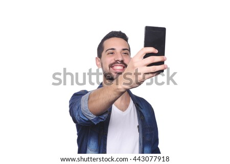 Portrait of attractive young man taking a selfie with his smartphone. Isolated white background. - stock photo