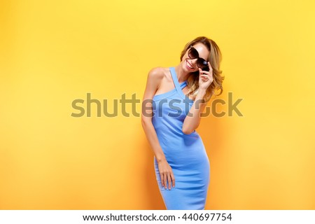 Portrait of attractive young model with blonde hair wearing blue dress against of yellow background.Isolated - stock photo