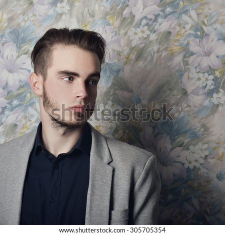 Portrait of attractive young mysterious man looking right at copy space, over floral background. Image toned. - stock photo
