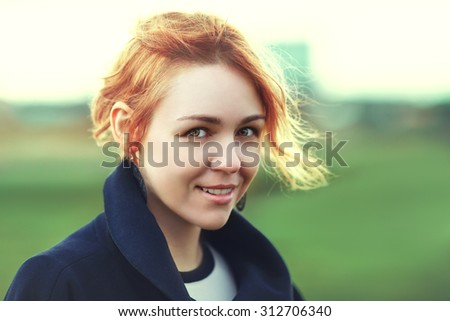 Portrait of attractive young red-haired woman in stylish clothes posing against countryside background in summer at sunset looking into camera smiling happily. Toned.  - stock photo