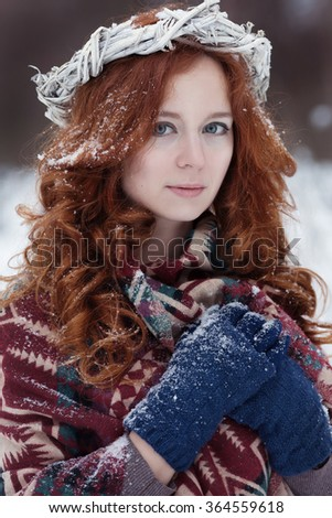 Portrait of attractive young redheaded woman. She is dressed in ethnic scarf and blue gloves. There is some snow in her hair. White wreath is on her head. - stock photo