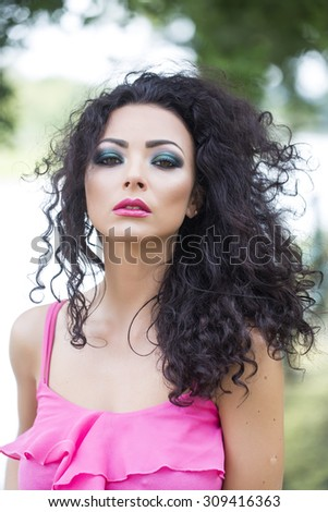 Portrait of attractive young sexual brunette girl with curly hair and bright makeup in pink clothes looking forward standing outdoor near fence in summer, vertical picture