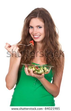 Portrait of attractive young smile woman eating vegetable salad, holding bowl and fork in hand, isolated over white background - stock photo