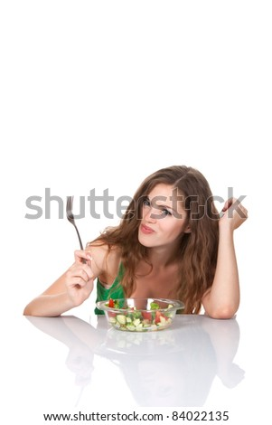 Portrait of attractive young smile woman eating vegetable salad, holding bowl and fork in hand, sitting at the table, isolated over white background