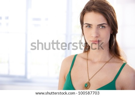 Portrait of attractive young woman front of window.