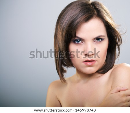 Portrait of attractive young woman. Hair in motion. Isolated on a gray background.