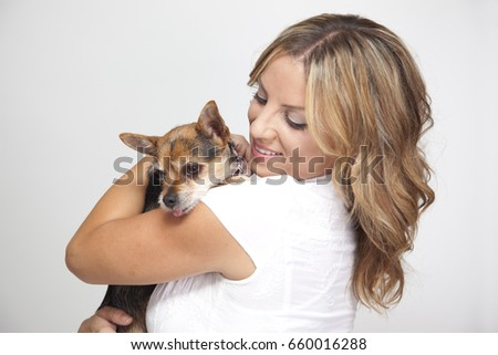 Portrait of attractive young woman hugging cute pet dog.