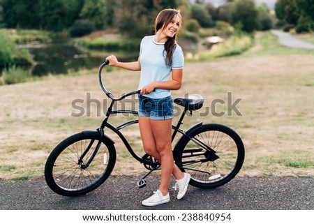 Portrait of Attractive Young Woman in blue shirt with cool beach cruiser bike looking away from camera smiling laughing wide - stock photo