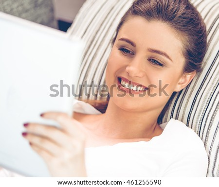 Portrait of attractive young woman in casual clothes using a digital tablet and smiling while lying on sofa at home