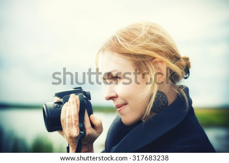 Portrait of attractive young woman in stylish clothes holding a camera taking photos on countryside in summer smiling. Vintage effect, soft-focus.  - stock photo