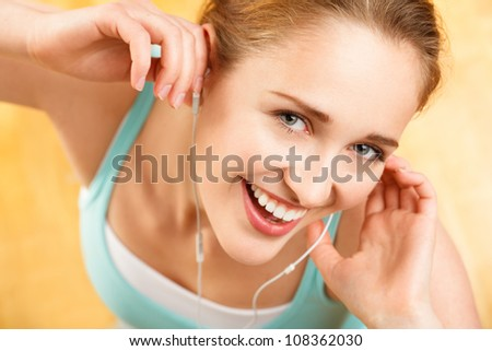 Portrait of attractive young woman listening to music at gym