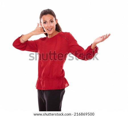 Portrait of attractive young woman on red shirt with call gesture holding her left hand up while smiling at you and standing on isolated studio